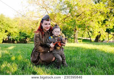 Mom And Son In A Military Soviet Soldier Uniform With St. George Ribbons Against The Backdrop Of Nat