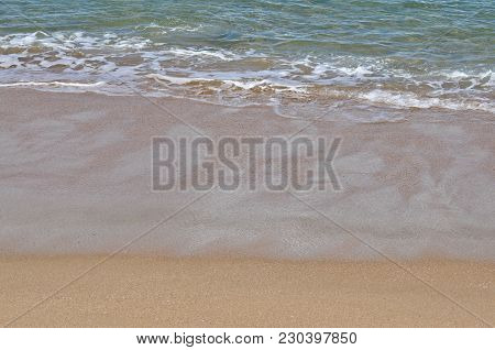 Small Waves Breaking At The Shoreline With Large Area Of Wet Sand.