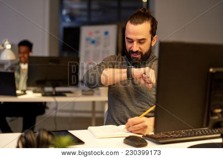 deadline, technology and people concept - creative man with smartwatch using voice command recorder and working late at night office