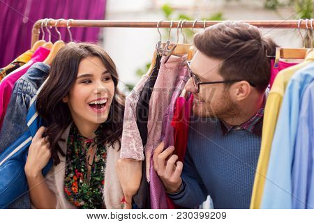 sale, shopping, fashion and people concept - happy couple having fun at vintage clothing store hanger