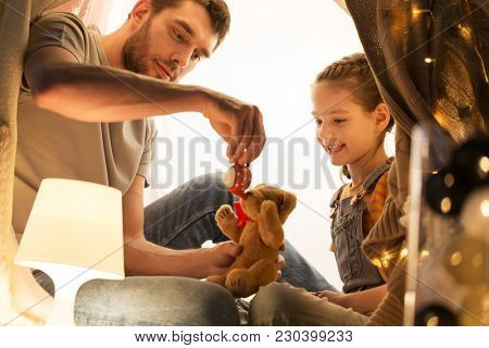 family, hygge and people concept - happy father and little daughter playing with teddy bear and toy tea pot in kids tent at night at home