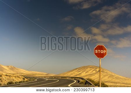 A Stop Sign On A Road In A Sand Desert