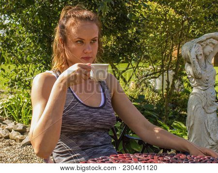 Young Woman With Sport Dress And Cup Of Coffee  In The Garden With A Sculpture