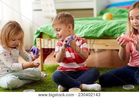 childhood, leisure and people concept - little kids with modelling clay or slimes at home