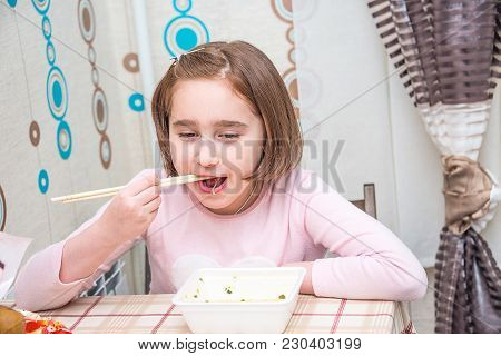 Child Is Eating Chinese Noodles For The Table, Disposable Tableware, Chopsticks,