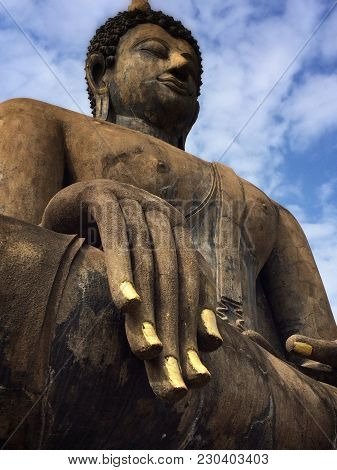 Ancient Buddha statue overlooking the ancient Thailand capital. Sukhithai sitting in the Zen position.