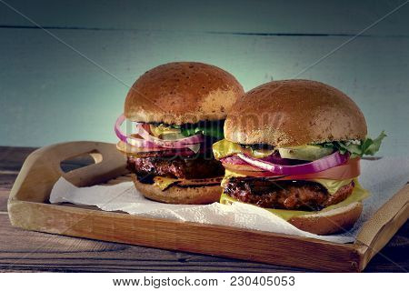 ?lose-up Of Two Tasty Hamburgers With Beef. Two Burgers Shot Close - Up On A Wooden Tray And Napkins