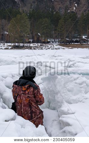 A Soldier In A Camouflage Jacket In The Snow Watching From An Ambush