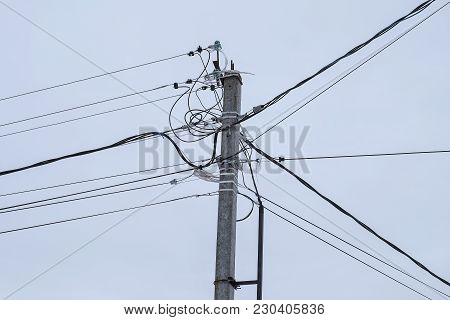 Post With Wires. On The Background Of Gray-blue Sky Cleared The Tip Of The Pole And Wires That Are I