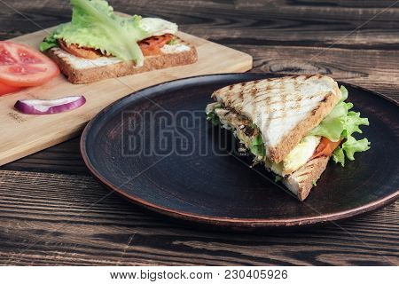 Sandwiches On Plates On A Wooden Surface. One Sandwich And Tomatoes With Onions On A Wooden Plate, T