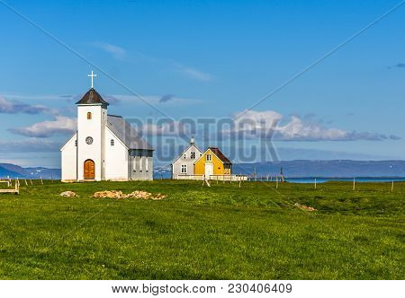 Flateyjarkirkja White Lutheran Church And Couple Of Living Huts With Meadow In Foreground And Sea  F