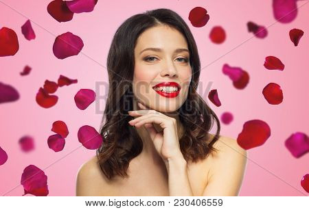 beauty, make up and people concept - happy smiling young woman with red lipstick posing over rose petals on background
