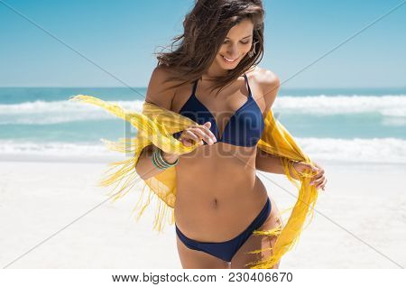 Beautiful young woman running on the beach with a yellow tissue. Happy smiling girl with scarf enjoying at beach. Freedom and carefree concept.