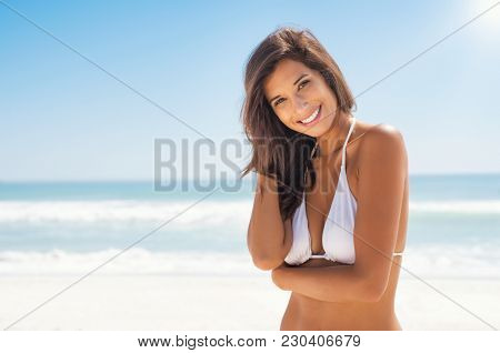 Beautiful young woman at beach looking at camera. Happy latin girl in white bikini smiling. Portrait of young tanned woman relaxing on beach with copy space and sea in background.