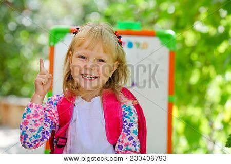 Little School Blonde Girl With A Backpack.