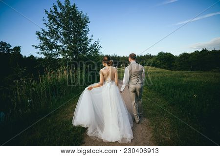 Stylish Bride And Groom Walking In The Park