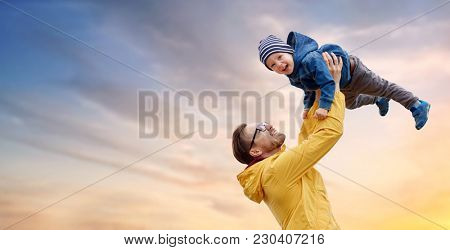 family, childhood and fatherhood concept - happy father and little son playing and having fun outdoors over evening sky background