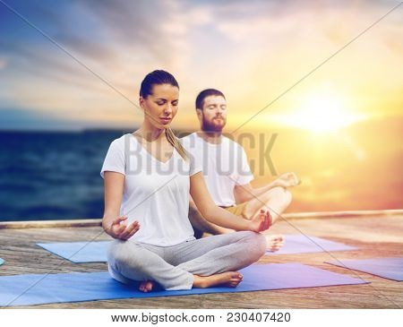 yoga and healthy lifestyle concept - people meditating in lotus pose on wooden pier over sea background