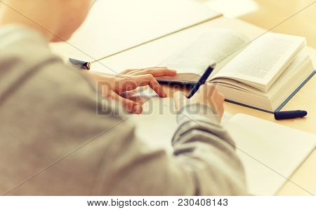 education, learning and people concept - close up of student boy with notebook and book writing school test