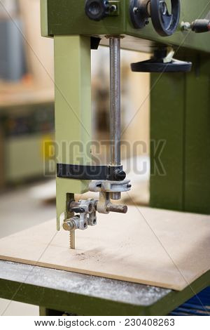 production, manufacture and woodworking industry concept - jig saw machine sawing board at workshop