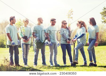 volunteering, charity, people and ecology concept - group of happy volunteers with tree seedlings and gardening tools in park