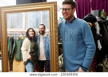 sale, shopping, fashion and people concept - happy smiling friends looking at mirror reflection at vintage clothing store
