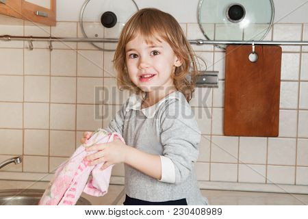 Baby Girl In The Kitchen Holds A Towel And Wipes Her Hands