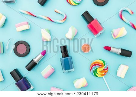 Feminine Cosmetics And Bright Sugar Candy On Blue Pastel Background. Top View. Flat Lay. Creativity