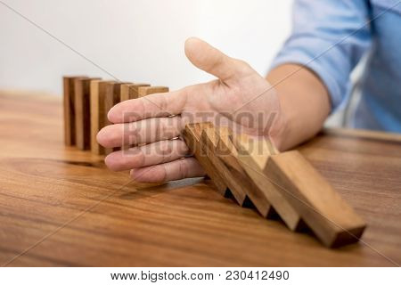 Risk And Strategy In Business, Close Up Of Businessman Hand Stopping Wooden Block From Falling In Th