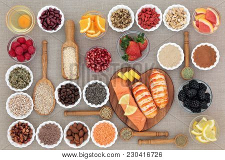 Healthy diet food concept with fresh seafood, fruit, vegetables, pulses, nuts, seeds, grains, dairy, cereals, coffee, nutritional supplement powders and herbs used appetite suppressants. Top view.