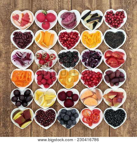 Anthocyanin health food concept with fruit, vegetable, pulses and grains in heart shaped bowls on rustic background.  Foods very high in anthocyanins, anthocyanins, vitamins and minerals.