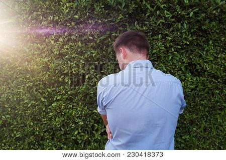 Back Pose, Photo Of Young Man Looks Ahead. He Feels Shame. He Is Alone And Hide His Face. Do Not Wan