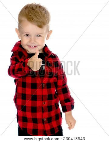 Little Boy Is Holding A Thumbs Up, In Studio On A White Background. The Concept Of Emotion And The A
