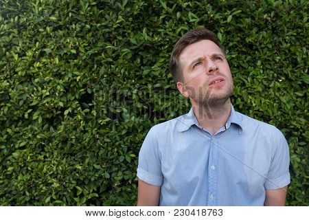 Successful Young Caucasian Man Looking To The Side Suspiciously On Green Tree Background. Concept Of