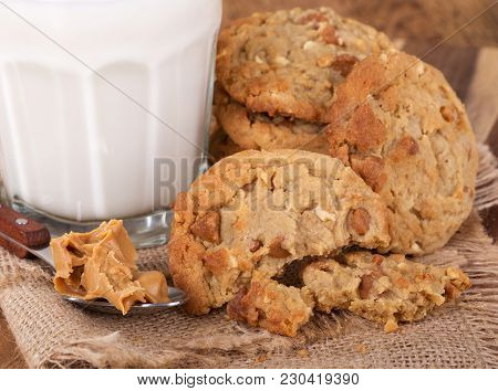 Closeup Of A Broken Peanut Butter Cookie And A Spoonful Of Peanut Butter With A Glass Of Milk