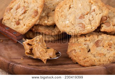Closeup Of A Spoonful Of Peanut Butter And A Pile Of Peanut Butter Cookies