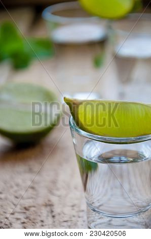 Alcohol Shot Drink. Silver Tequila With Lime On The Wooden Table.