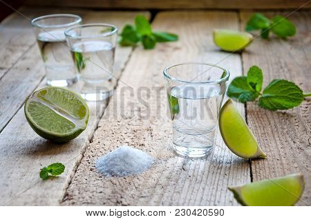 Alcohol Shot Drink. Silver Tequila With Lime, Salt And Green On The Wooden Table.