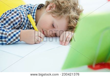 Tired Little Boy Sitting At The Table, With Hishead On His Arm, Writing In Her Notebook While Doing