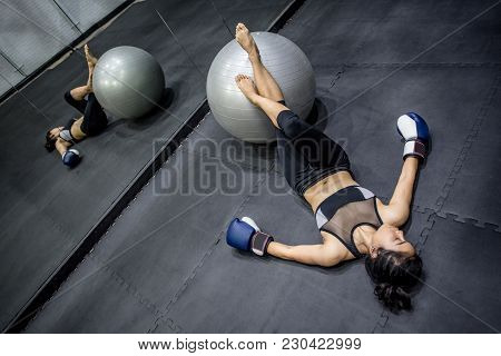 Young Asian Woman Wearing Sportswear And Boxing Gloves Laying On The Floor With Exercise Ball In Fit