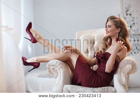 Beautiful Sexy Lady In An Elegant Burgundy Dress. Close Up Fashion Portrait Of Model Indoors. Beauty