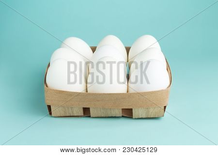 Chicken Eggs In A Wooden Package. Nine White Eggs In A Box On A Blue Background