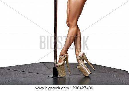 Closeup Of Beautiful Legs On Gloden High Heels. Pole Dance Standing On Pylon. Isolated Studio Shot.