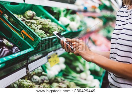 Young Woman Shopping Purchase Healthy Food In Supermarket Blur Background. Close Up View Girl Blogge