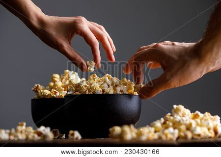 Hands Reach For A Bowl With Tasty Popcorn.