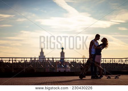 Outdoor Shot Of Affectionate Young Couple Pose Against Beautiful City View And Sky, Have Rest After
