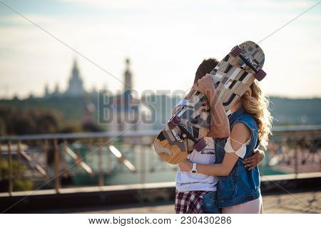 Lovely Couple Of Active Skateboarders Embrace And Kiss Passionately, Hide Themselves Behind Skateboa
