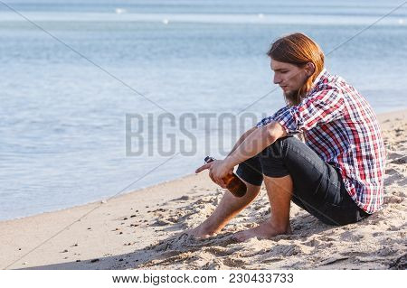 Man Depressed With Wine Bottle Sitting On Beach Outdoor. People Abuse And Alcoholism Problems