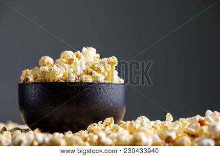 Popcorn In A Black Ceramic Cup And Around It.