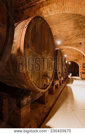 Ancient Gigantic Wine Barrels In The Basement Of The  Monte Oliveto Maggiore Abbey. Asciano, Provinc